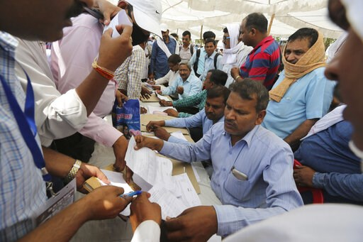(AP Photo/Rajesh Kumar Singh). Election officers crowd around a distribution center to receive electronic voting machines for their respective polling stations on the eve of polling in Prayagraj, India, Saturday, May 11, 2019. The sixth phase of the se...