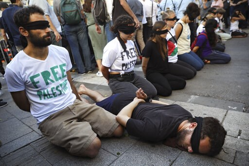 (AP Photo/Oded Balilty). Peace activists protest before the presentation of the 2019 Eurovision Song Contest participants in Tel Aviv, Israel, Sunday, May 12, 2019.