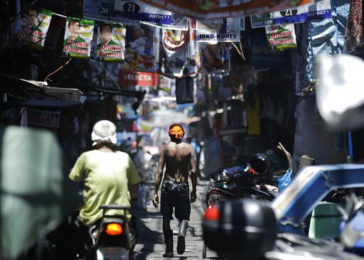 (AP Photo/Aaron Favila). In this Thursday, May 9, 2019, photo, a man walks past election banners in the slum district of Tondo, Manila, Philippines. Philippine President Rodrigo Duterte's name is not on the ballot but Monday's mid-term elections are se...