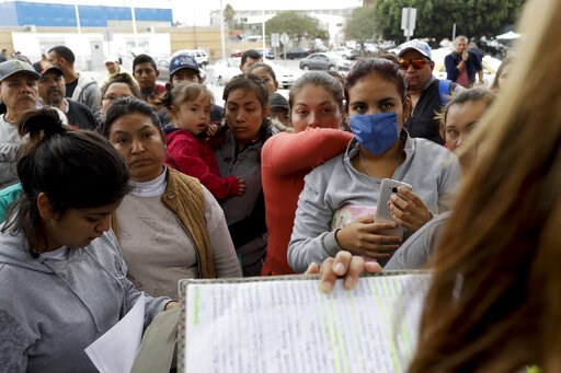 (AP Photo/Gregory Bull, File). FILE - In this Oct. 23, 2018, file photo, women in Tijuana, Mexico, look on as numbers and names are called to from a list of asylum seekers who want to cross the border into the United States. Tijuana is the busiest bord...