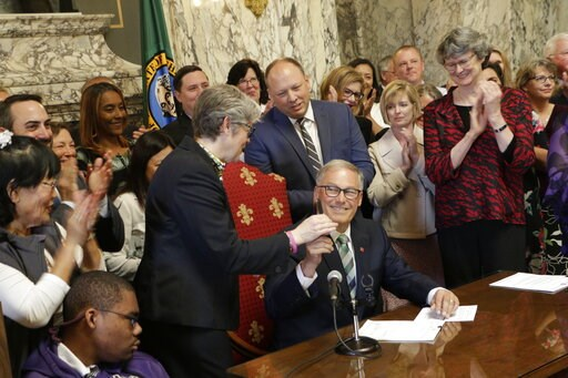 (AP Photo/Rachel La Corte). Gov. Jay Inslee, seated, hands Democratic Rep. Laurie Jinkins his pen after he signed a measure that makes Washington the first state in the nation to establish a program to help offset the costs of long-term care, Monday, M...