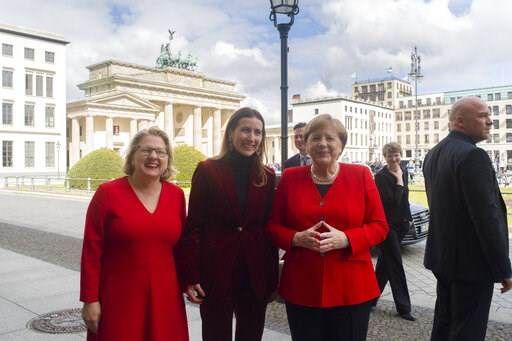 (AP Photo/Markus Schreiber). German Chancellor Angela Merkel,right, German Environment Minister Svenja Schulze, left, and Chilean Environment Minister Carolina Schmidt, center, pose for media in front of the Brandenburg Gate prior to a session of the 1...