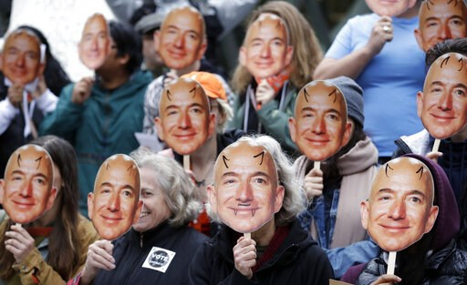 "(AP Photo/Elaine Thompson, File). FILE - In this Oct. 31, 2018, file photo, demonstrators hold images of Amazon CEO Jeff Bezos near their faces during a Halloween-themed protest at Amazon headquarters over the company's facial recognition system, ""Reko..."