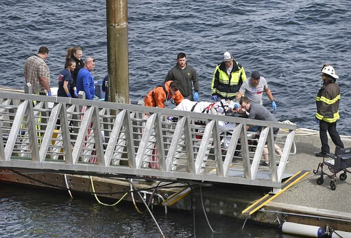 (Dustin Safranek/Ketchikan Daily News via AP). Emergency response crews transport an injured passenger to an ambulance at the George Inlet Lodge docks, Monday, May 13, 2019, in Ketchikan, Alaska. The passenger was from one of two sightseeing planes rep...