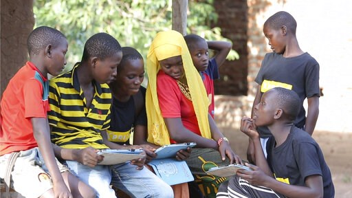(Courtesy XPRIZE via AP). In this undated photo provided by XPRIZE, children in a village in the Tanga region of Tanzania gather to learn from tablets using open-sourced software that would easily be downloaded by illiterate children to teach themselve...