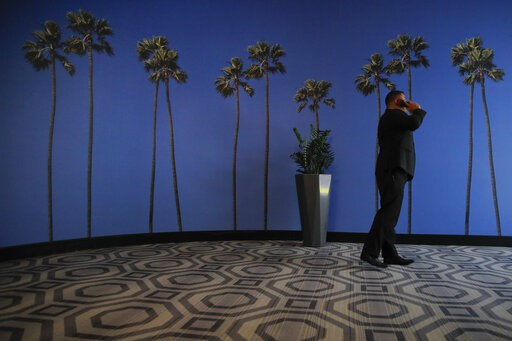 (AP Photo/Jae C. Hong, File). FILE - In this May 4, 2018, file photo a man talks on the phone in a hallway adorned with the palm tree-printed wallpaper at a hotel near the Los Angeles International Airport in Los Angeles. U.S. regulators are proposing ...