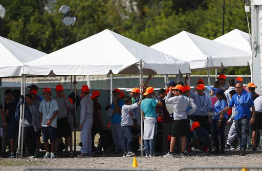 (AP Photo/Wilfredo Lee, File). FILE - In this Monday, May 6, 2019 file photo, migrant children stand outside the Homestead Temporary Shelter for Unaccompanied Children in Homestead, Fla. The U.S. government is providing long-distance video counseling t...