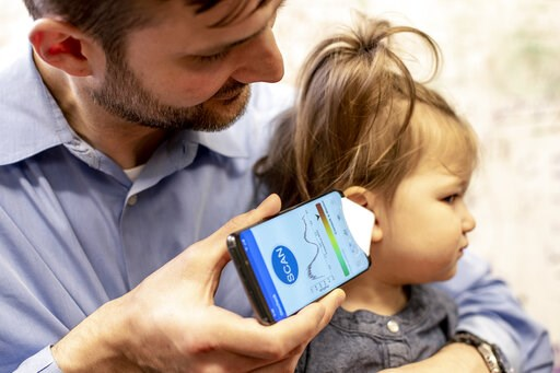 (Dennis Wise/University of Washington via AP). In this undated photo provided by the University of Washington in May 2019, Dr. Randall Bly uses a uses a phone app and a paper funnel to focus the sound, to check his daughter for an ear infection, at the...