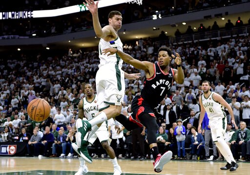 (Frank Gunn/The Canadian Press via AP). Toronto Raptors guard Kyle Lowry (7) passes the ball under pressure from Milwaukee Bucks forward Nikola Mirotic (41) during the second half in Game 1 of the NBA basketball playoffs Eastern Conference final in Mil...