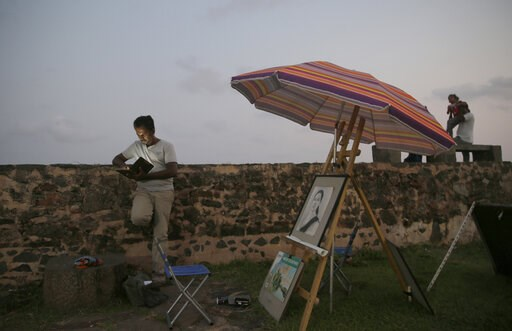 (AP Photo/Eranga Jayawardena). In this Friday, May 10, 2019, photo, a Sri Lankan street painter looks at his mobile phone as locals stand along the 17th century Dutch built rampart of the Galle fort in Galle, Sri Lanka. Sri Lanka was the Lonely Planet ...