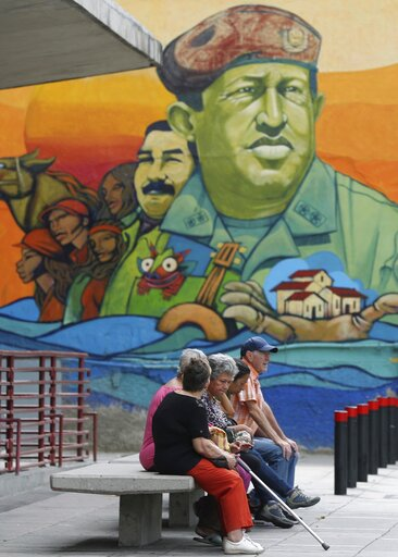 (AP Photo/Martin Mejia). Residents rest on a bench backdropped by a mural featuring Venezuela's late President Hugo Chavez and President Nicolas Maduro, in Caracas, Venezuela, Friday, May 3, 2019. In the fourth month of their standoff, Maduro and oppos...