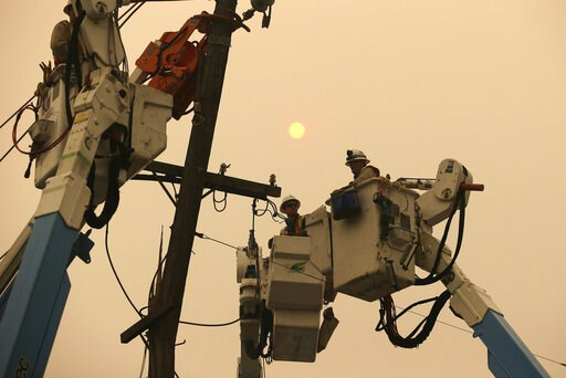 (AP Photo/Rich Pedroncelli, File). FILE - In this Nov. 9, 2018 file photo, Pacific Gas & Electric crews work to restore power lines in Paradise, Calif. Some investors call PG&E the first climate change bankruptcy. It filed for Chapter 11 protec...