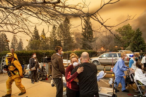 (AP Photo/Noah Berger, File). FILE - This Nov. 8, 2018, file photo shows Nurse Cassie Lerossignol hugs as coworker as the Feather River Hospital burns while the Camp Fire rages through Paradise, Calif. California fire authorities say that Pacific Gas a...