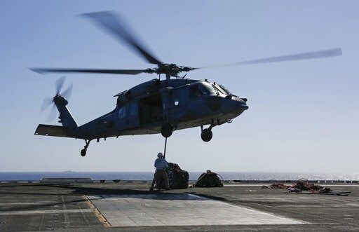 (Mass Communication Specialist 3rd Class Amber Smalley, U.S. Navy via AP). In this Friday, May 10, 2019 photo released by the U.S. Navy, logistics specialists attach cargo to an MH-60S Sea Hawk helicopter on the flight deck of the Nimitz-class aircraft...