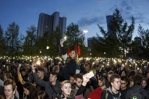 (AP Photo/Anton Basanayev). Demonstrators wave their cell phones as they gather in front of a new built fence blocked by police, during a protest against plans to construct a cathedral in a park in Yekaterinburg, Russia, Wednesday, May 15, 2019. Hundre...