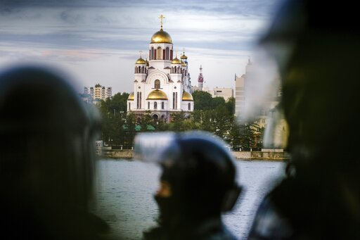 (AP Photo/Anton Basanayev). Riot police stand next to demonstrators gather in front of a newly built fence blocked by police, during a protest against plans to construct a cathedral in a park with the Church on the Blood, a cathedral erected on a place...