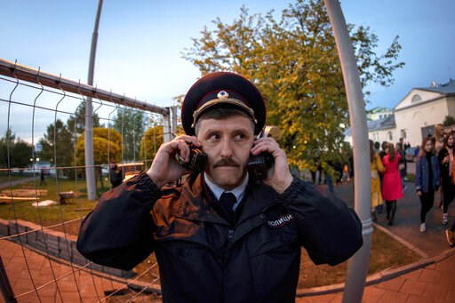 (AP Photo/Anton Basanayev). A police officer speaks on two walkie talkies as demonstrators gather in front of a new builded fence blocked by police to protest plans to construct a cathedral in a park in Yekaterinburg, Russia, Wednesday, May 15, 2019. H...