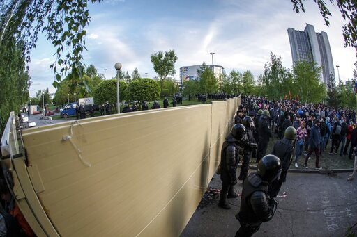 (AP Photo/Anton Basanayev). Demonstrators gather in front of a new builded fence blocked by police, to protest plans to construct a cathedral in a park in Yekaterinburg, Russia, Wednesday, May 15, 2019. Hundreds of riot police have surrounded a park in...