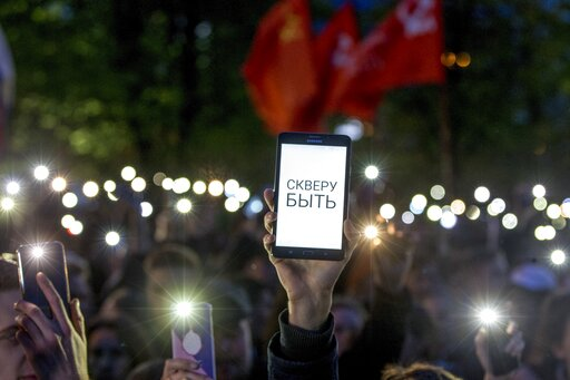 """(AP Photo/Anton Basanayev). Demonstrators wave their cell phones, with the words on one of them reading """"Park has to be! """" as they gather in front of a new builded fence blocked by police protesting plans to construct a cathedral in a park in Yekaterin..."""
