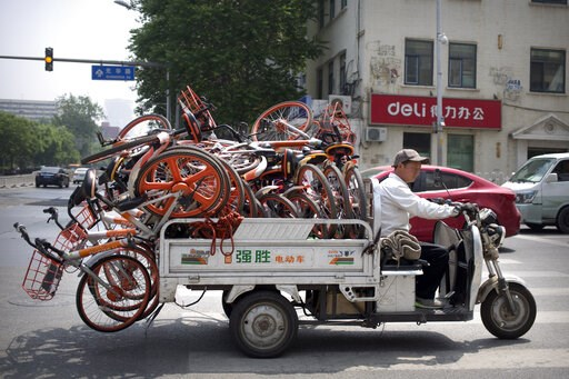 (AP Photo/Mark Schiefelbein). A worker uses an electric cart to haul a load of ride-sharing bicycles along a street in Beijing, Thursday, May 16, 2019. Figures released on Wednesday showed China's factory output and consumer spending weakened in April ...