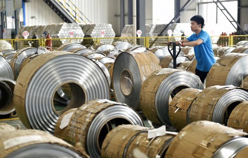 (Chinatopix via AP). In this Wednesday, May 15, 2019, photo, a worker moves aluminum pipes in a factory in Zouping in eastern China's Shandong province. Figures released on Wednesday showed China's factory output and consumer spending weakened in April...