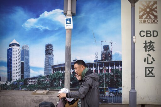 (AP Photo/Mark Schiefelbein). A man uses his mobile phone in front of a billboard at a construction site in Beijing, Thursday, May 16, 2019. Figures released on Wednesday showed China's factory output and consumer spending weakened in April as a tariff...