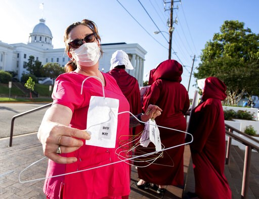 (Mickey Welsh/The Montgomery Advertiser via AP). Laura Stiller hands out coat hangers as she talks about illegal abortions during a rally against a ban on nearly all abortions outside of the Alabama State House in Montgomery, Ala., on Tuesday, May 14, ...