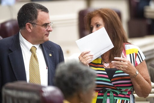 (Mickey Welsh/Montgomery Advertiser via AP). Rep. Terri Collins, right, chats with Rep. Chris Pringle on the house floor at the Alabama Statehouse in Montgomery, Ala., on Tuesday May 14, 2019. Alabama lawmakers are expected to vote on a proposal to out...