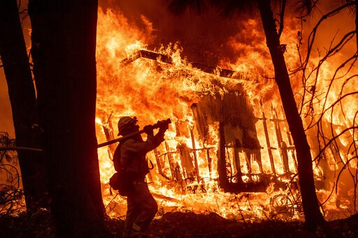 (AP Photo/Noah Berger, File). FILE - In this Nov. 9, 2018 file photo, firefighter Jose Corona sprays water as flames from the Camp Fire consume a home in Magalia, Calif. Federal officials say an effort to develop a better fire shelter following the dea...