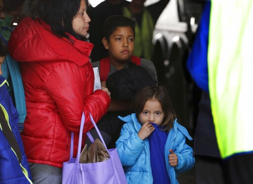 (AP Photo/Eric Gay, File). FILE - In this April 2, 2019, file photo, immigrants from Central America seeking asylum board a bus in San Antonio. The Trump administration has alerted two counties in Florida to prepare for an influx of immigrants at the b...