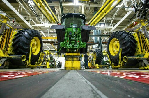 (Zach Boyden-Holmes/Telegraph Herald via AP, File). FILE - In this April 9, 2019, wheels are attach as workers assemble a tractor at John Deere's Waterloo, Iowa assembly plant. Deere & Co. reports earnings on Friday, May 17.