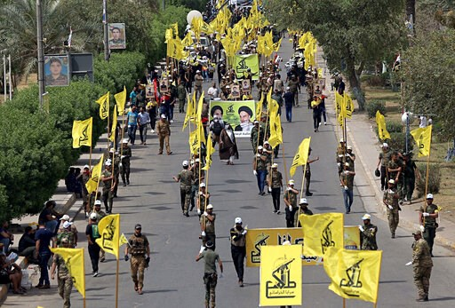 """(AP Photo/Hadi Mizban, File). FILE - In this June 8, 2018 file photo, Iraqi Popular Mobilization Forces march as they hold their flag and posters of Iraqi and Iranian Shiites spiritual leaders during """"al-Quds"""" or Jerusalem Day, in Baghdad, Iraq. When U..."""