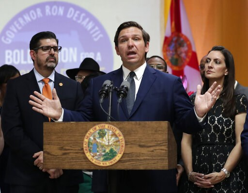 (AP Photo/Lynne Sladky, File). FILE- In this May 9, 2019 file photo. Florida Gov. Ron DeSantis, second from right, speaks during a bill signing ceremony at the William J. Kirlew Junior Academy, in Miami Gardens, Fla. Gov. DeSantis said Friday, May 17, ...