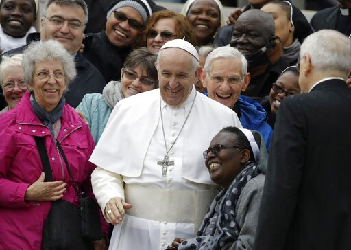 (AP Photo/Andrew Medichini). Pope Francis shares a laugh with a group of faithful as he poses for a family photo, at the end of his weekly general audience in St. Peter's Square, at the Vatican, Wednesday May 15, 2019.