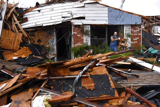 (Ronald W. Erdrich/The Abilene Reporter-News via AP). Wesley Mantooth lifts a wooden chair out a window of the home of his father, Robert, in Abilene, Texas, on Saturday, May 18, 2019. Many residents said a tornado struck in the early morning hours.