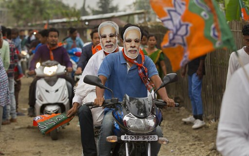 (AP Photo/Anupam Nath, File). FILE - In this April 2, 2019 file photo, Bharatiya Janata Party (BJP) supporters wear masks of Indian Prime Minister Narendra Modi and ride a motorbike during an election campaign rally ahead of general elections in Borhol...