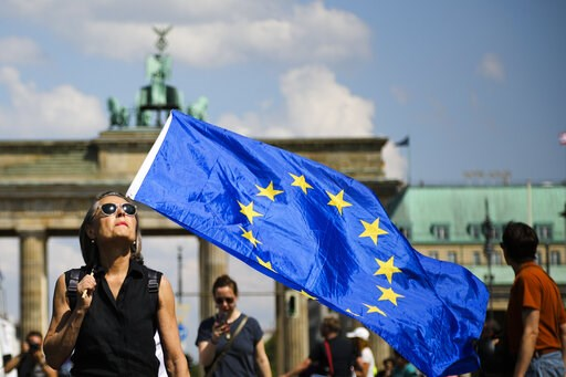(AP Photo/Markus Schreiber). A woman holds a European flag as she attends a demonstration in Berlin, Germany, Sunday, May 19, 2019. People across Europe attend demonstrations under the slogan 'A Europe for All - Your Voice Against Nationalism'.