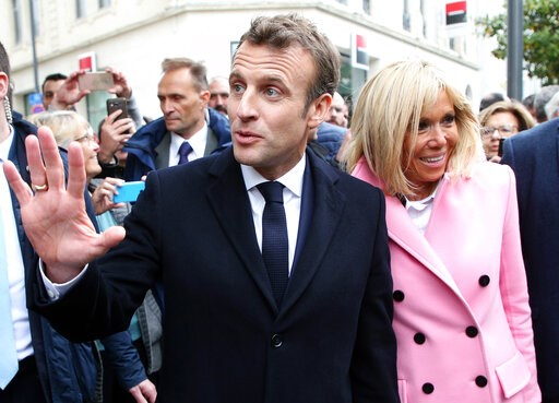(AP Photo/Bob Edme). France's President Emmanuel Macron gestures as he walks with his wife Brigitte during a visit to Biarritz, southwestern France, Friday, May 17, 2019.
