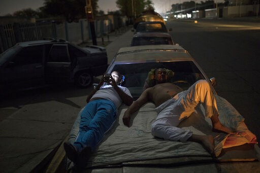 (AP Photo/Rodrigo Abd). Andres Quintero, left, and Fermin Perez rest on top of Perez's car as they wait in line for over 20 hours to fill their tanks with gas in Cabimas, Venezuela, Thursday, May 16, 2019. U.S. sanctions on oil-rich Venezuela appear to...