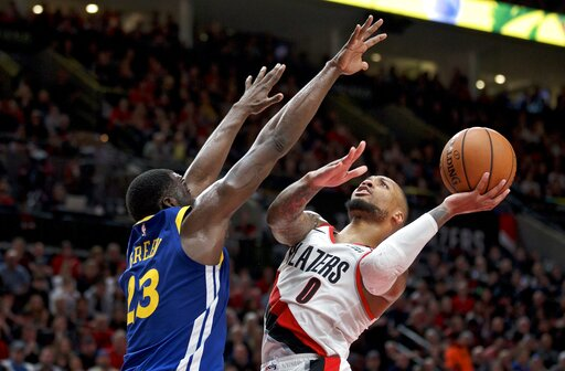 (AP Photo/Craig Mitchelldyer). Portland Trail Blazers guard Damian Lillard, right, shoots over Golden State Warriors forward Draymond Green during the second half of Game 3 of the NBA basketball playoffs Western Conference finals Saturday, May 18, 2019...