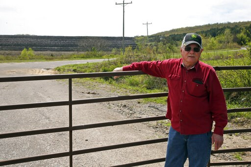 (AP Photo/Sue Ogrocki). In this April 8, 2019, photo, Tim Tanksley, who has been fighting for years trying to convince Oklahoma lawmakers to crack down on the coal ash dumping, stands outside a dump site in Bokoshe, Okla. President Donald Trump's EPA h...