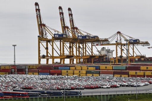 (AP Photo/Martin Meissner). Cars for export and import are stored in front of containers on Thursday, May 16, 2019 at the harbor in Bremerhaven, Germany, with 2 million vehicles per annum one of the largest automobile hubs in the world. US President Do...