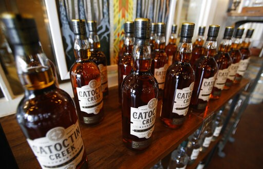 (AP Photo/Steve Helber, File). FILE - In this June 20, 2018 file photo, Catoctin Creek Distillery whiskey is on display in a tasting room in Purcellville, Va. American whiskey producers feeling the pain from the Trump administration's trade disputes ha...
