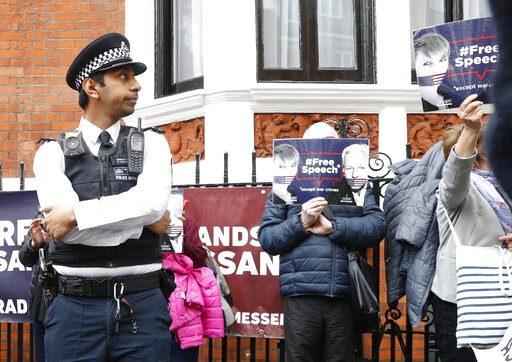 (AP Photo/Alastair Grant). British police arrive and guard the Ecuadorian Embassy as protesters in support of Wikileaks founder Julian Assange demonstrate outside the embassy in London, Monday, May 20, 2019. Swedish authorities on Monday issued a reque...