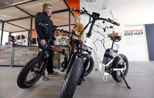 (AP Photo/Elaine Thompson). In this photo taken Wednesday, May 15, 2019, customer Torre Treece, left, talks with Rad Power Bikes sales associate Becs Richards about the two electric bikes he bought at the shop in Seattle. The bicycle company said that ...