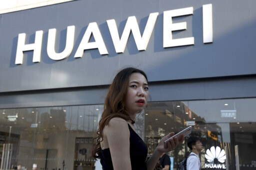 (AP Photo/Ng Han Guan). A woman uses a smartphone outside a Huawei store in Beijing Monday, May 20, 2019. Google is assuring users of Huawei smartphones the American company's services still will work on them following U.S. government restrictions on d...