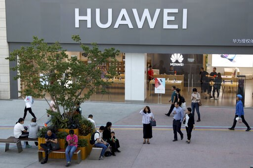 (AP Photo/Ng Han Guan). A woman gets her bearing outside a Huawei store in Beijing Monday, May 20, 2019. Google is assuring users of Huawei smartphones the American company's services still will work on them following U.S. government restrictions on do...
