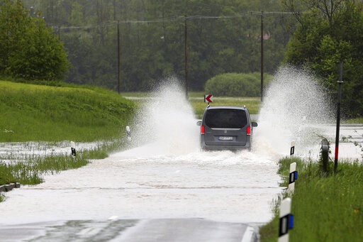 (AP Photo/Matthias Schrader). A car makes his way through a flooded road near Marquartstein, Germany, Tuesday, May 21, 2019.