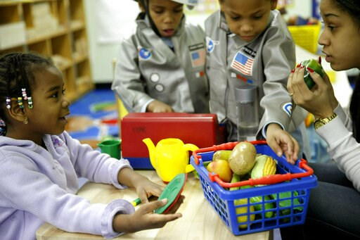 (AP Photo/Seth Wenig). FILE - In this Tuesday, Jan. 21, 2014 file photo, Oumou Balde, 4, left, plays with her teacher Jacqualine Sanchez, right, and some pretend food in a pre-kindergarten class at the Sheltering Arms Learning Center in New York in a p...