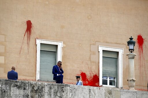 (AP Photo/Thanassis Stavrakis). Policemen stand in front of the Parliament building as red paint is seen on the wall in Athens, Tuesday, May 21, 2019. A group of about 10 people threw red paint at parliament and set off a smoke bomb as Greece's Supreme...